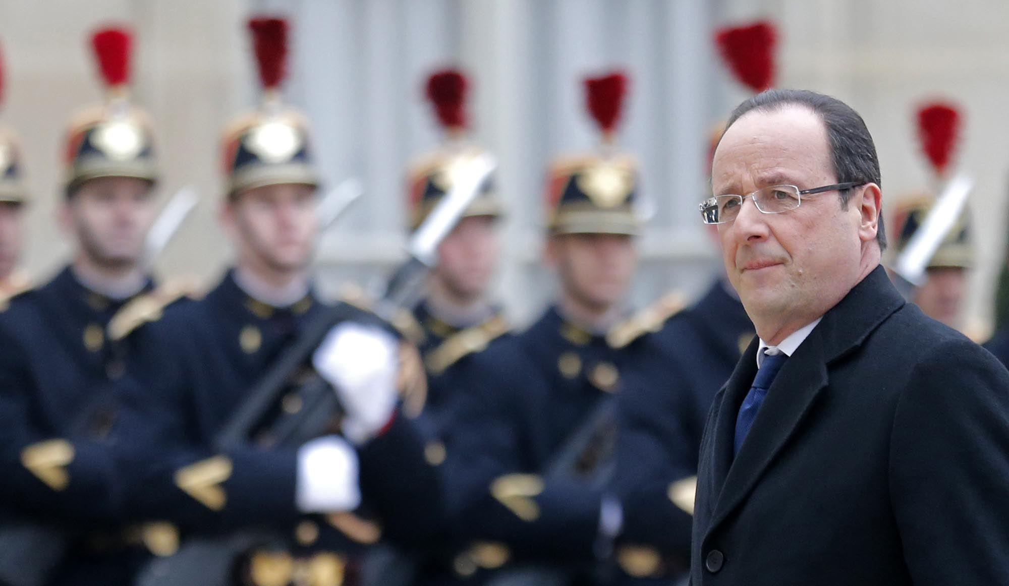 French President Francois Hollande walks past the honour guard as he arrives for a meeting with a guest at the Elysee Palace in Paris