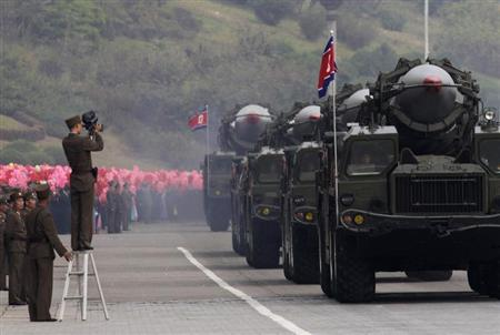 A North Korean soldier films military vehicles carrying missiles during a parade to commemorate the 65th anniversary of founding of the Workers' Party of Korea in Pyongyang