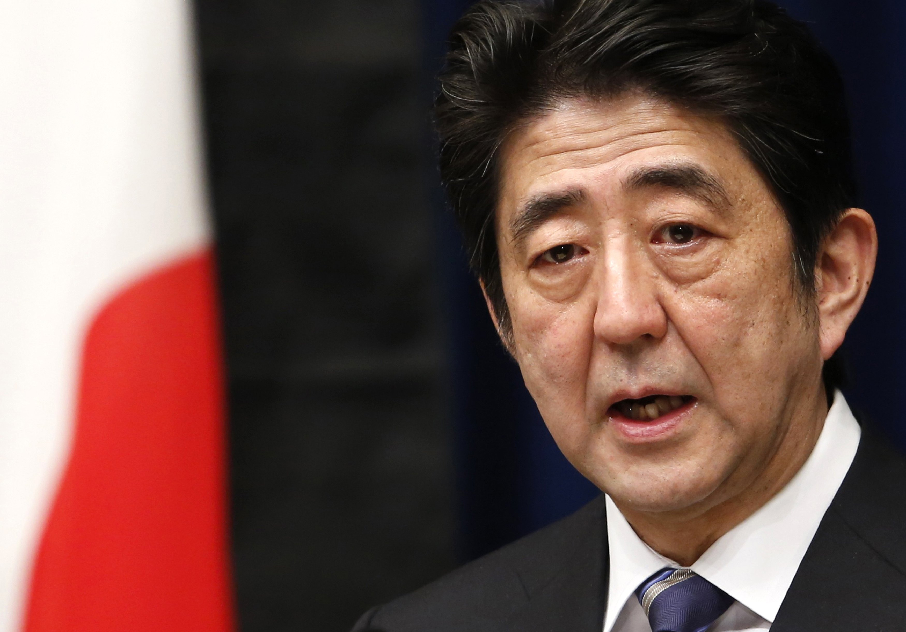 File photo Japan's PM Shinzo Abe speaking next to the national flag, which is hung with a black ribbon as a symbol of mourning for victims of the March 11, 2011 earthquake and tsunami, in Tokyo