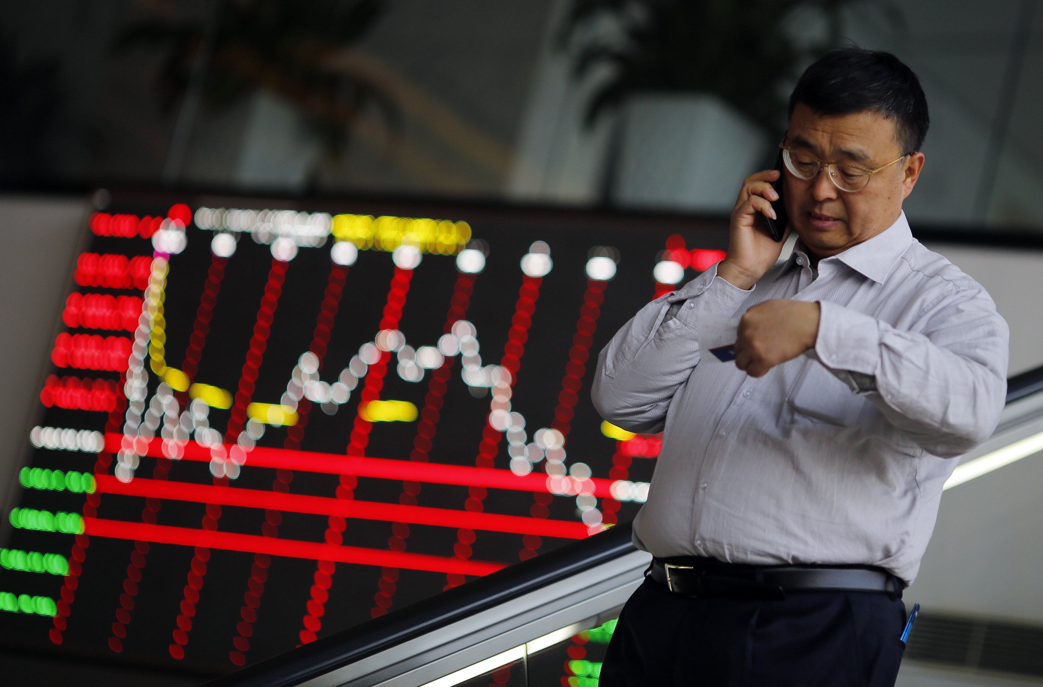 A man talks on the phone inside the Shanghai Stock Exchange building at the Pudong financial district in Shanghai