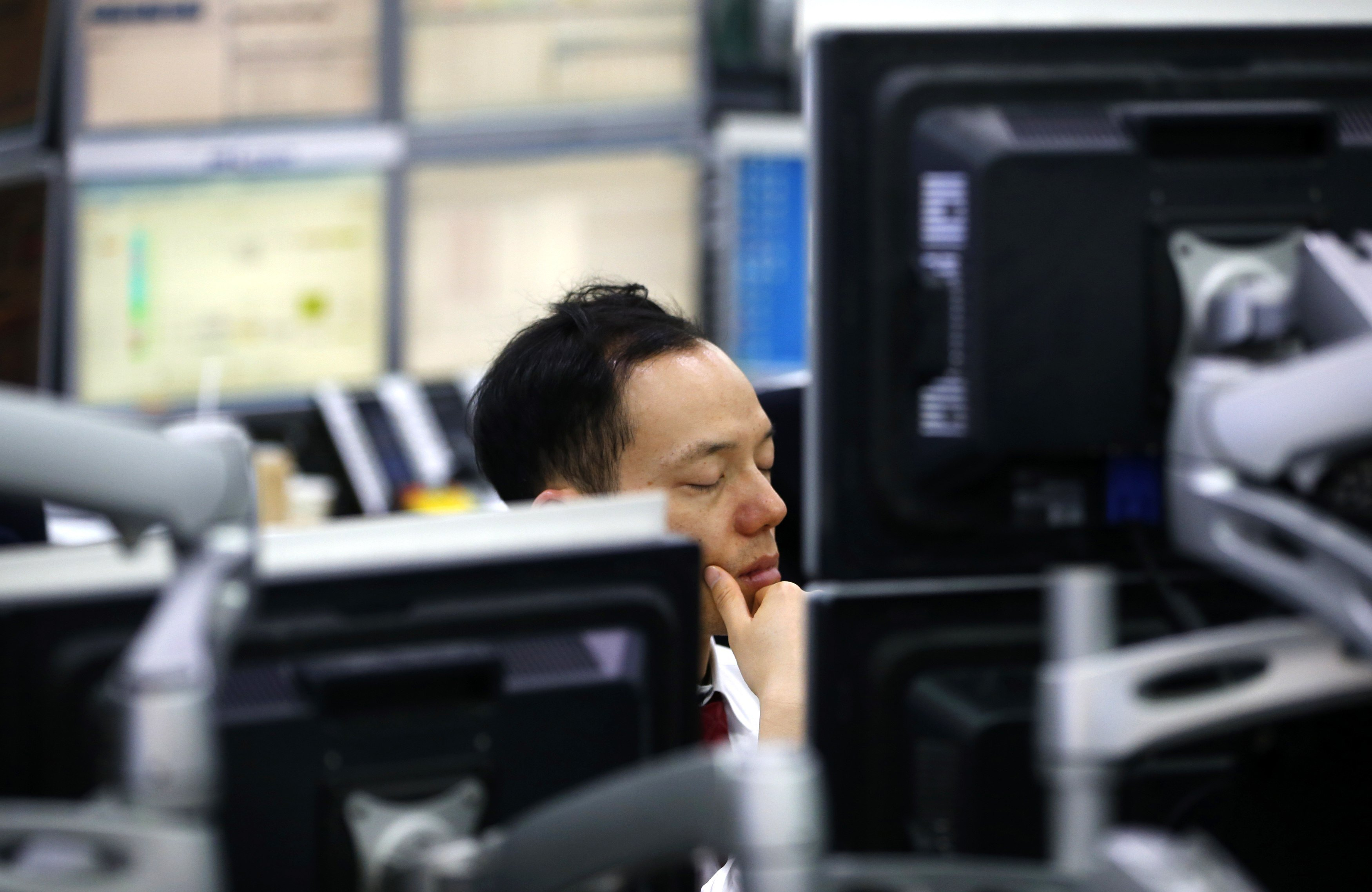 A currency dealer sleeps in front of screens as he works at a dealing room of a bank in Seoul
