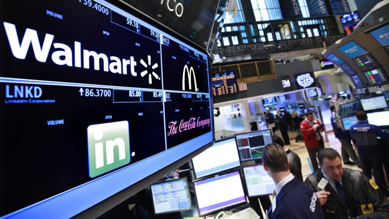 File photo of a board showing stock prices for Walmart, Linkedin, McDonald's and Coca-Cola at a booth on the floor of the New York Stock Exchange