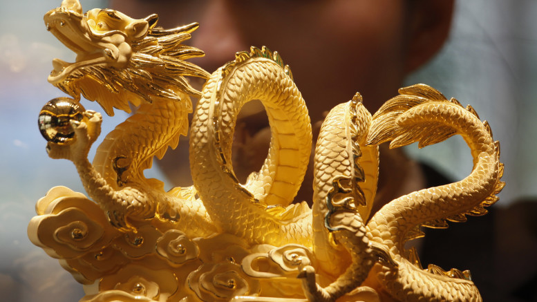 "Sales representative poses behind nine-tael 24K gold in shape of dragon forming numerals ""2012"", symbolizing upcoming Year of the Dragon, at a Chow Tai Fook Jewellery store in Hong Kong"