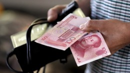 File photo of a customer holding 100 Yuan notes at a market in Beijing